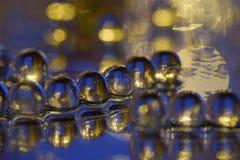 Foco seleccionado de las bolas de cristal de azul y de amarillo en la superficie del espejo imagenes de archivo