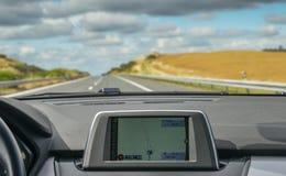 Foco selectivo de construido en el navegador de GPS en tablero de instrumentos de un coche que va abajo de la carretera escénica  Fotos de archivo libres de regalías