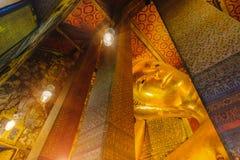 Foco selectivo de la cara de la estatua de oro de descanso de Buda con arquitectura tailandesa del arte en la iglesia Wat Pho Fotos de archivo
