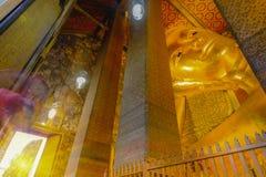 Foco selectivo de la cara de la estatua de oro de descanso de Buda con arquitectura tailandesa del arte en la iglesia Wat Pho Imágenes de archivo libres de regalías