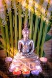 Foco selectivo de la estatua de Buda con el lig ardiente borroso de la vela Fotos de archivo