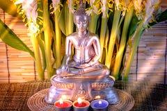 Foco selectivo de la estatua de Buda con el lig ardiente borroso de la vela Imagen de archivo libre de regalías