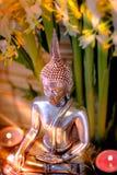 Foco selectivo de la estatua de Buda con el lig ardiente borroso de la vela Foto de archivo libre de regalías