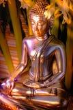 Foco selectivo de la estatua de Buda con el lig ardiente borroso de la vela Fotografía de archivo libre de regalías