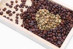 Foco selectivo de la forma del corazón del grano de café en isolat de madera de la bandeja Imagen de archivo libre de regalías