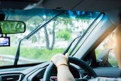 Foco selectivo de la mujer que conduce un coche con la gotita de la lluvia en el viento imágenes de archivo libres de regalías