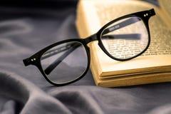 Foco selectivo de las lentes de la lectura con el libro abierto Fotos de archivo libres de regalías