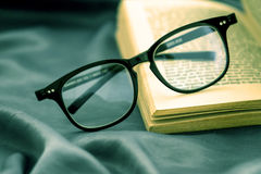 Foco selectivo de las lentes de la lectura con el libro abierto Foto de archivo libre de regalías