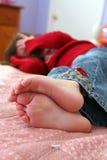 Foco selectivo de los pequeños pies descubiertos de la niña Imagen de archivo
