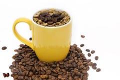 Foco selectivo del grano de café en taza amarilla en el fondo blanco Fotografía de archivo