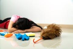 Foco selectivo del plumero de la pluma Las amas de casa asiáticas mienten en el piso debido cansarse de tareas de hogar Con el di imagenes de archivo