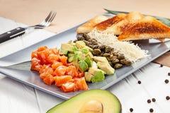 Foco selectivo delicioso en tartare de color salmón con el aguacate y la tostada en el fondo blanco imagen de archivo libre de regalías