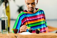 Foco selectivo en camarero mexicano hermoso en poncho colorido Fotografía de archivo libre de regalías