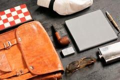 Foco selectivo en el sistema de un viajero - gafas de sol, cuaderno, pluma, bolso de cuero, tubo, tablero de ajedrez del día de f Imagen de archivo