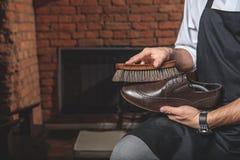 Foco selectivo en el zapato con el cepillo en manos del zapatero Fotos de archivo libres de regalías