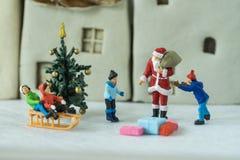Foco selectivo en la figura miniatura Papá Noel que da actual t Imagenes de archivo