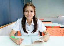 Foco selectivo en la lectura tailandesa del estudiante de mujeres jovenes en biblioteca Foto de archivo libre de regalías