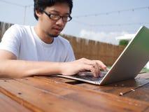 Foco selectivo en las manos del hombre asiático que mecanografían en el teclado del ordenador portátil Foto de archivo libre de regalías
