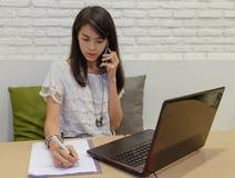 Foco selectivo en las mujeres adultas tailandesas que trabajan con el ordenador portátil en casa Fotos de archivo
