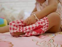 Foco selectivo en los pantalones cortos como pequeño bebé asiático que aprende ponerlo sola imagen de archivo libre de regalías