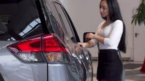 Foco selectivo en luces del coche, mujer que elige el nuevo auto en la representación almacen de metraje de vídeo