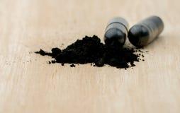 Foco selectivo en polvos del carbón de leña activado en la tabla de madera marrón Foto de archivo libre de regalías