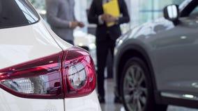 Foco selectivo en un coche, vendedor que habla con el cliente en el fondo metrajes