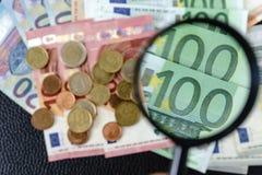 Foco selectivo, lupa en billetes de banco euro con el euro c Foto de archivo libre de regalías