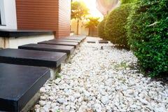 Foco seletivo da maneira de passeio das rochas pretas no jardim tropical Fotografia de Stock Royalty Free