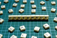 Foco seletivo da palavra do consenso feito do bloco quadrado da letra no fundo quadrado verde da esteira imagens de stock