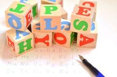 Foco seletivo de letras inglesas com o isolado da pena no fundo branco para o conceito do inglês do estudo Cubos com letras fotos de stock royalty free