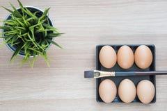 Foco seletivo de seis ovos na placa do quadrado preto com uma escova Fotografia de Stock