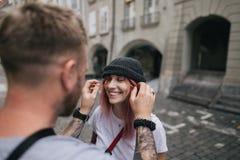 foco seletivo do homem que põe o chapéu sobre a jovem mulher de sorriso bonita ao andar junto na rua em Berna foto de stock royalty free