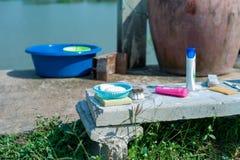 Foco seletivo do sabão na cesta plástica e da escova para a lavanderia com a garrafa plástica do champô posta sobre o assoalho co foto de stock royalty free