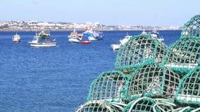 Foco seletivo e de-foco de armadilhas do marisco e de barcos de pesca na ba?a de Cascais, Portugal vídeos de arquivo