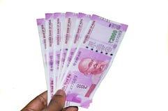 Foco seletivo: Mão que mantém 2000 notas indianas da rupia contra o fundo branco Feche acima da cédula 2000 nova da rupia no home fotos de stock