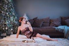 Foco seletivo na mulher bonita de sorriso que veste o vestido de noite agradável que guarda um vidro que felicita nos com o ano n Fotografia de Stock Royalty Free