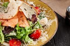 Foco seletivo na salada de Caesar servida com os salmões no fundo escuro fotografia de stock
