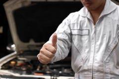 Foco seletivo nas mãos do homem novo profissional do mecânico que mostra o polegar acima como o sinal do sucesso com o carro na c Foto de Stock Royalty Free