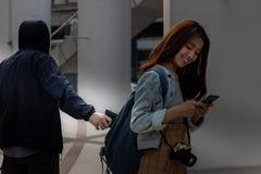 Foco seletivo nas mãos do ladrão do carteirista que roubam a carteira da trouxa da menina do turista fotografia de stock royalty free