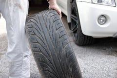Foco seletivo nas mãos do mecânico automotivo no pneu guardando uniforme para o carro de fixação no fundo da garagem do reparo fotografia de stock royalty free