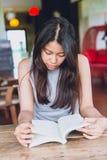 Foco serio adolescente tailandés de las mujeres asiáticas para leer el libro de bolsillo en cafetería Fotografía de archivo