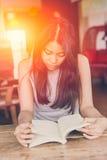 Foco serio adolescente tailandés de las mujeres asiáticas para leer el libro de bolsillo en cafetería Fotografía de archivo libre de regalías