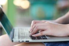 Foco suave de la mujer joven del freelancer que trabaja usando el ordenador port?til en cafeter?a, tecnolog?a de comunicaci?n y n fotos de archivo