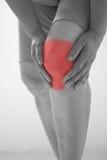 Foco suave de viejas mujeres asiáticas a la lesión de rodilla en el fondo blanco Imagen de archivo