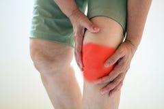 Foco suave de viejas mujeres asiáticas a la lesión de rodilla en el fondo blanco Foto de archivo