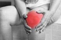 Foco suave de viejas mujeres asiáticas a la lesión de rodilla en el fondo blanco Fotografía de archivo