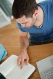 Focos del estudiante en su libro Imagen de archivo libre de regalías