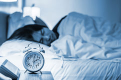 Focus on the alarm clock in front of sleeping man at night. In the bedroom Royalty Free Stock Photo