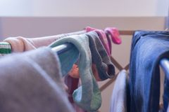Focus on ankle socks drying on a laundry rack with other woman`s clothes, including blue jeans. Mismatched socks and pair of stock photos